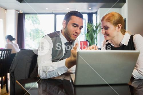 Two business people in a restaurant working together