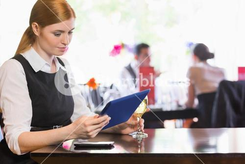 Businesswoman looking at tablet screen while holding wine glass