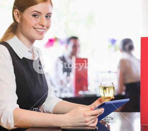 Attractive businesswoman holding tablet and wine glass and smiling