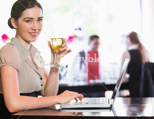 Happy businesswoman holding wine glass using laptop and looking at camera