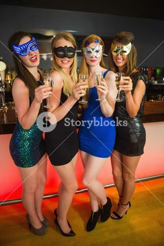 Happy friend with masks on holding champagne
