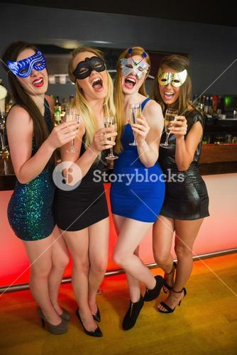 Laughing friends with masks on holding champagne