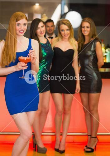 Beautiful woman standing in front of her friends holding cocktail