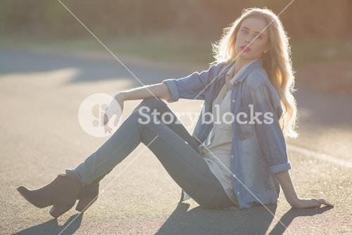 Fashionable woman sitting on road and posing