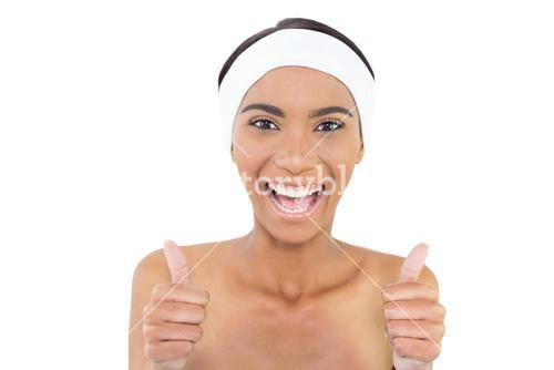 Smiling gorgeous model wearing headband giving thumbs up to camera