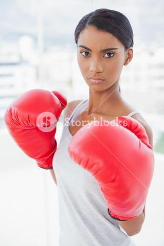 Competitive serious model wearing red boxing gloves