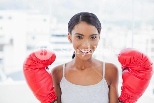 Cheerful competitive model with boxing gloves posing