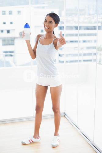 Cheerful sporty model giving thumbs up to camera