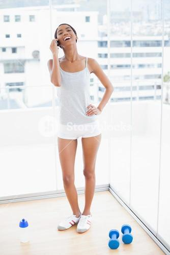 Cheerful sporty model having a phone call
