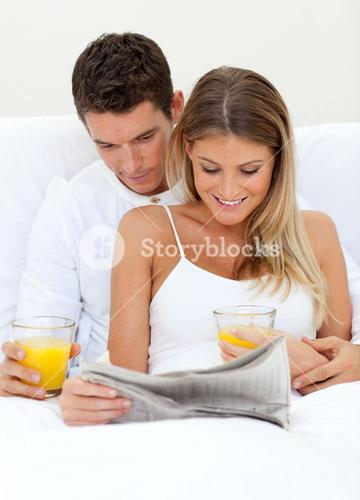 Lovers reading a newspaper and drinking orange juice