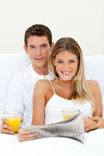 Young couple reading a newspaper and drinking orange juice