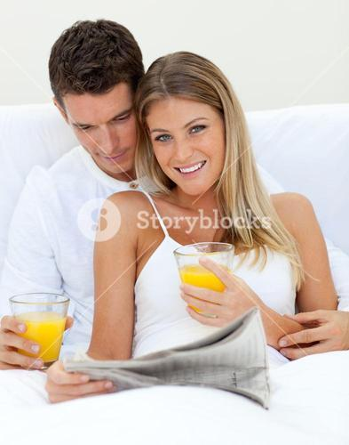 Loving couple reading a newspaper and drinking orange juice