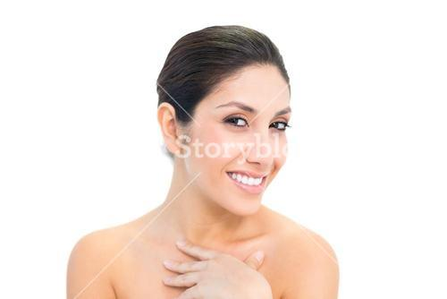 Smiling brunette looking at camera with hand on chest