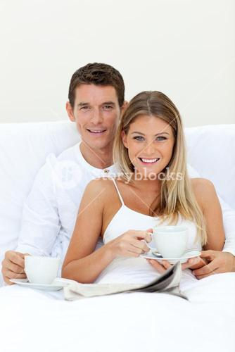 Romantic couple drinking coffee lying on their bed