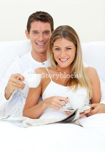 Happy couple drinking coffee lying on their bed