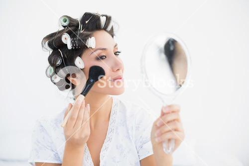 Pretty brunette in hair rollers holding hand mirror and applying makeup