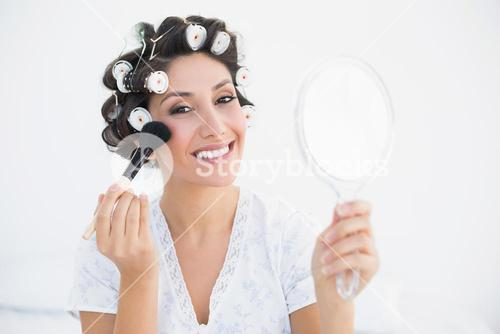 Smiling brunette in hair rollers holding hand mirror and applying makeup
