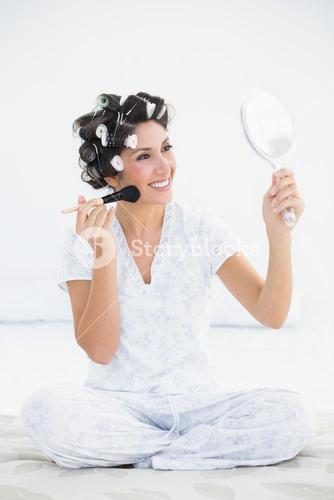 Cheerful brunette in hair rollers holding hand mirror and applying makeup