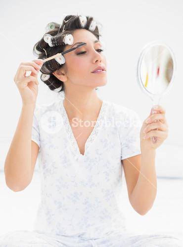 Happy brunette in hair rollers looking in hand mirror and brushing her eyebrows