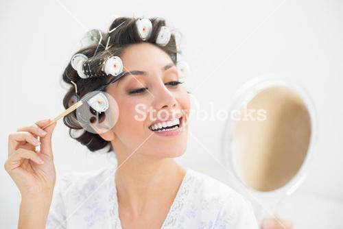 Smiling brunette in hair rollers looking in hand mirror and brushing her eyebrows