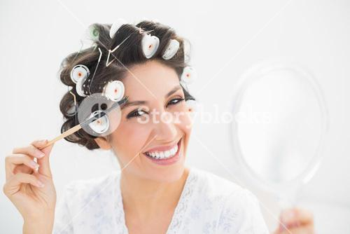 Pretty brunette in hair rollers holding hand mirror and brushing her eyebrows