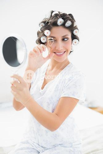 Pretty brunette in hair rollers looking in hand mirror and using eyelash curler