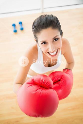 Fit woman wearing red boxing gloves smiling at camera