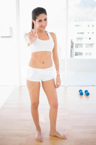 Fit confident woman smiling at camera and pointing