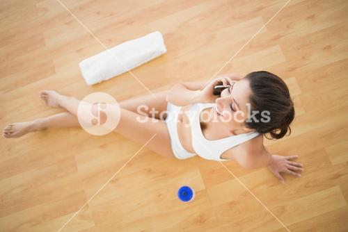 Fit happy woman taking a call during her workout