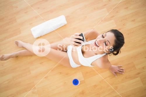 Fit happy woman sending a text during her workout