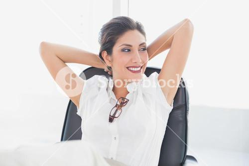 Reclining businesswoman sitting at her desk smiling