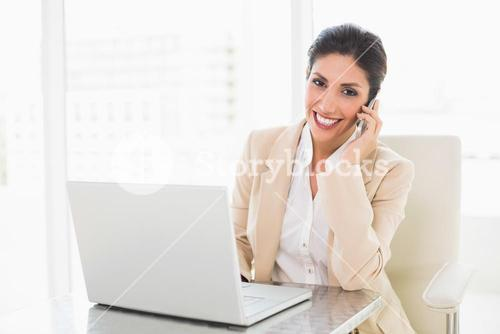 Happy businesswoman working with a laptop on the phone