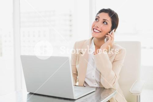 Cheerful businesswoman working with a laptop on the phone
