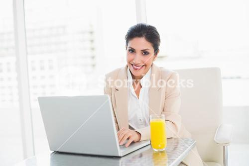 Happy businesswoman with laptop and glass of orange juice at desk