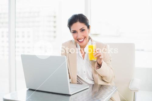 Cheerful businesswoman with laptop and glass of orange juice at desk