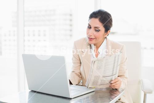 Happy businesswoman reading newspaper while working on laptop