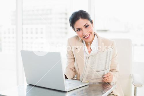 Smiling businesswoman holding newspaper while working on laptop