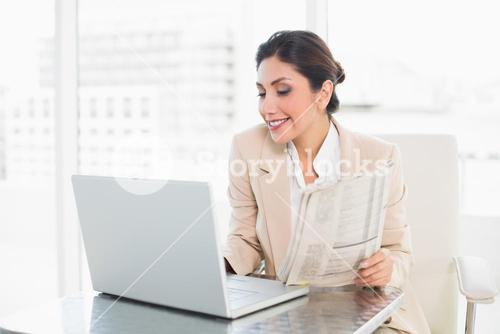 Cheerful businesswoman holding newspaper while working on laptop