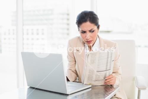 Serious businesswoman reading newspaper while working on laptop