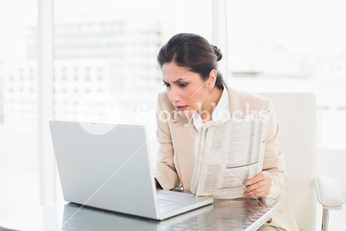 Stern businesswoman holding newspaper while working on laptop