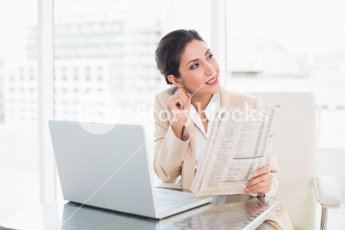 Smiling businesswoman holding newspaper while working on laptop looking away