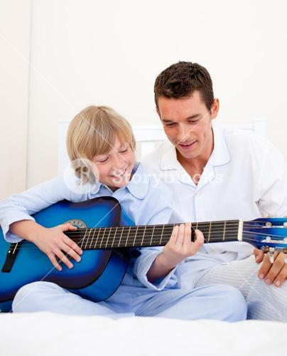 Smiling little boy playing guitar with his father