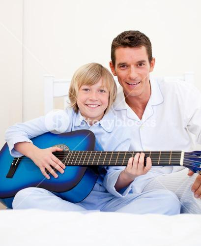 Merry little boy playing guitar with his father