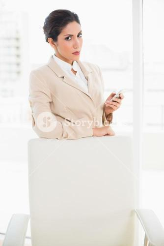 Frowning businesswoman standing behind her chair holding her phone glaring at camera