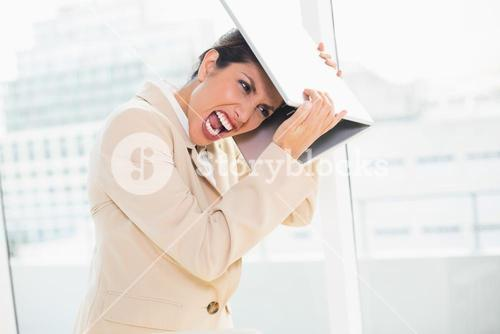 Crazed businesswoman hitting head off laptop