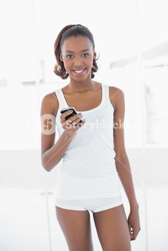 Cheerful fit woman text messaging