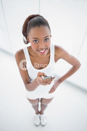 High angle view of cheerful fit woman text messaging