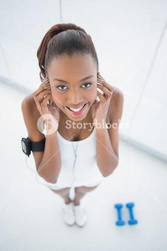 High angle view of smiling fit woman listening to music