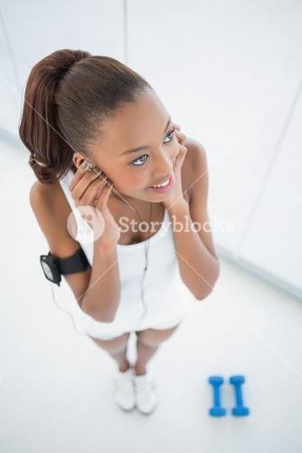 High angle view of happy fit woman listening to music