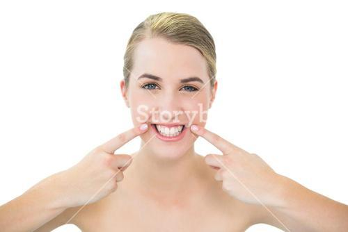 Pretty blonde pointing at mouth wrinkle